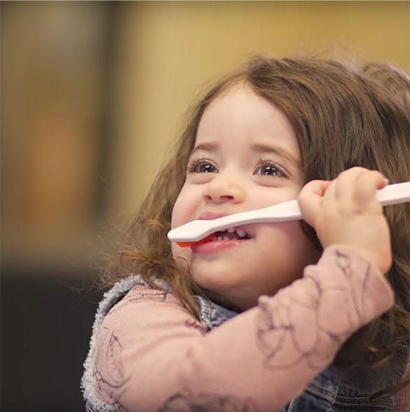 toddler brushing her teeth with questionable technique