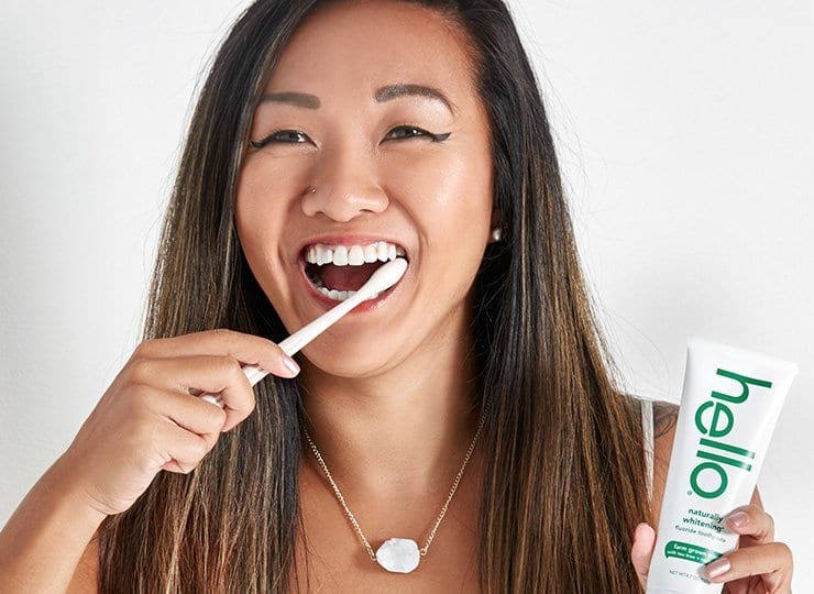 woman brushing with naturally whitening toothpaste