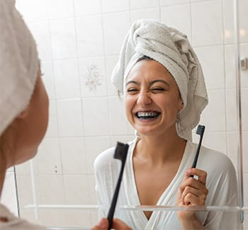 woman smiling while brushing with charcoal toothpaste
