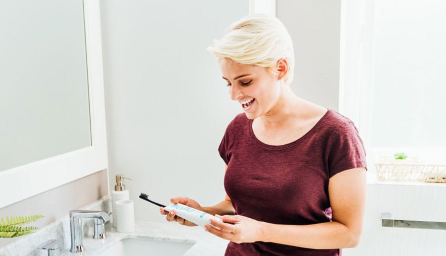 woman smiling at her toothpaste